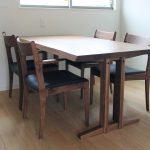 シンプルな2本脚構造のテーブルと愛らしい肘形状のチェア